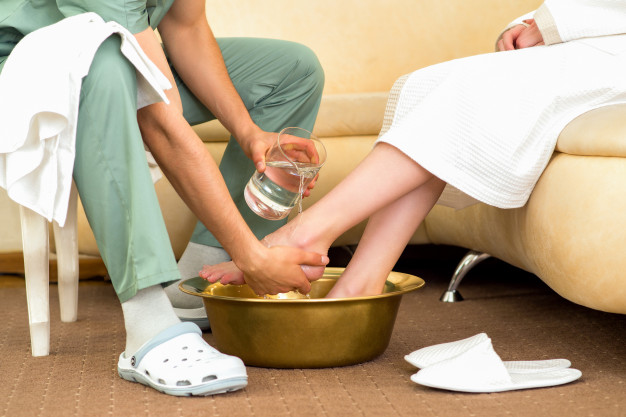 El terapeuta de masaje lava los pies de la mujer. | Foto Premium